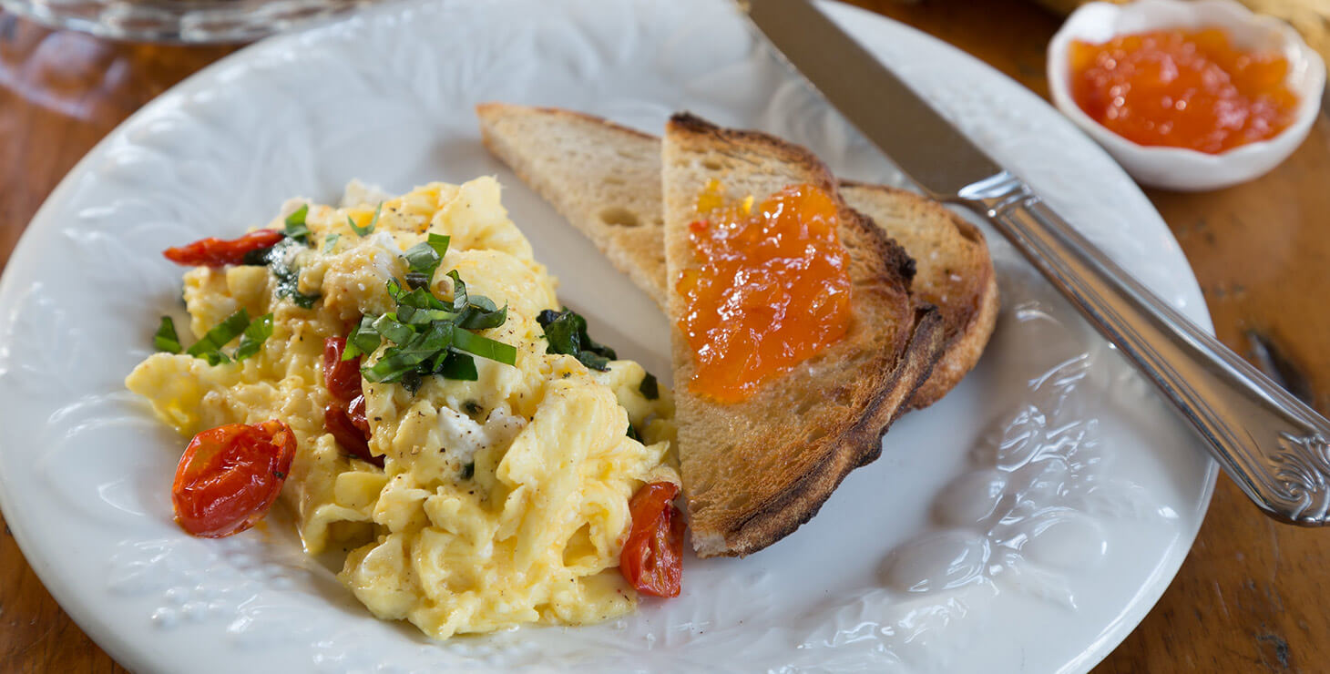 Scrambled eggs and toast with jelly