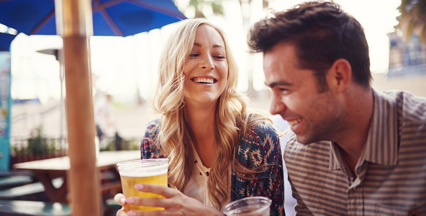 Couple laughing and drinking beers
