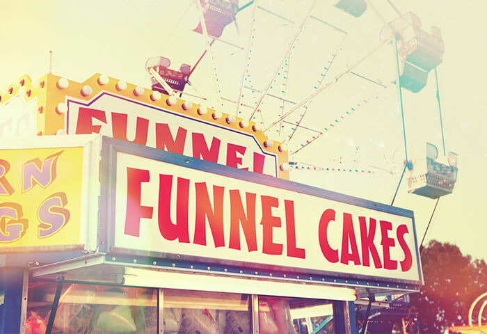 Funnel cake stand and Ferris wheel at a fair