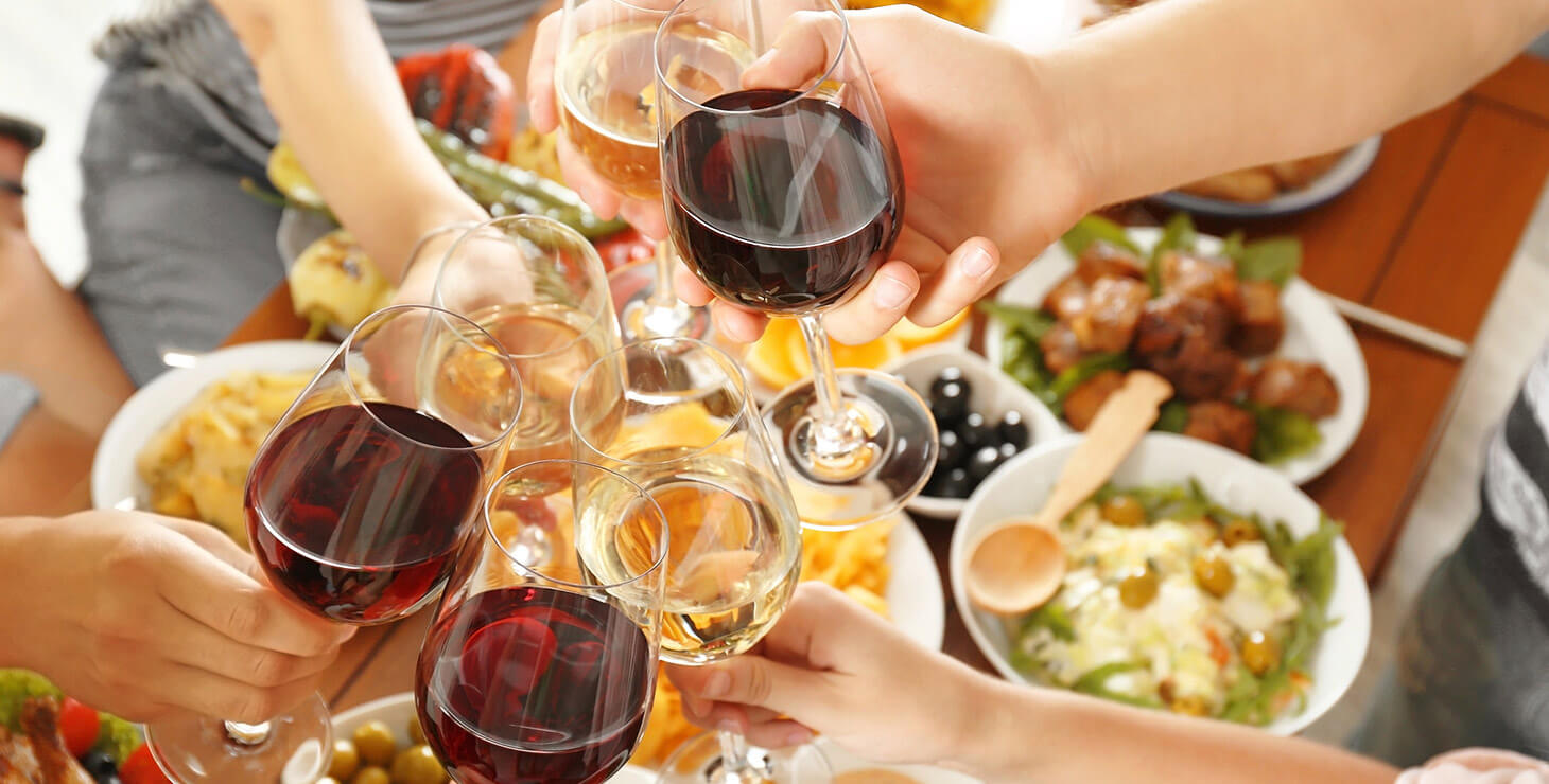 Toasting with wine glasses over a table of food