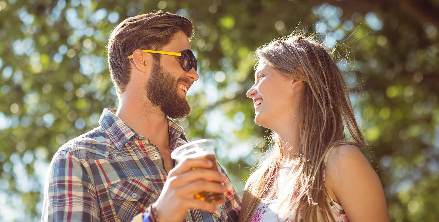 Couple smiling and drinking beer at a festival