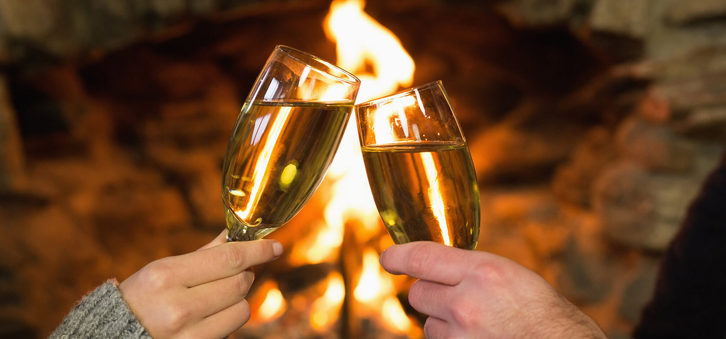Champagne glasses in front of the fire
