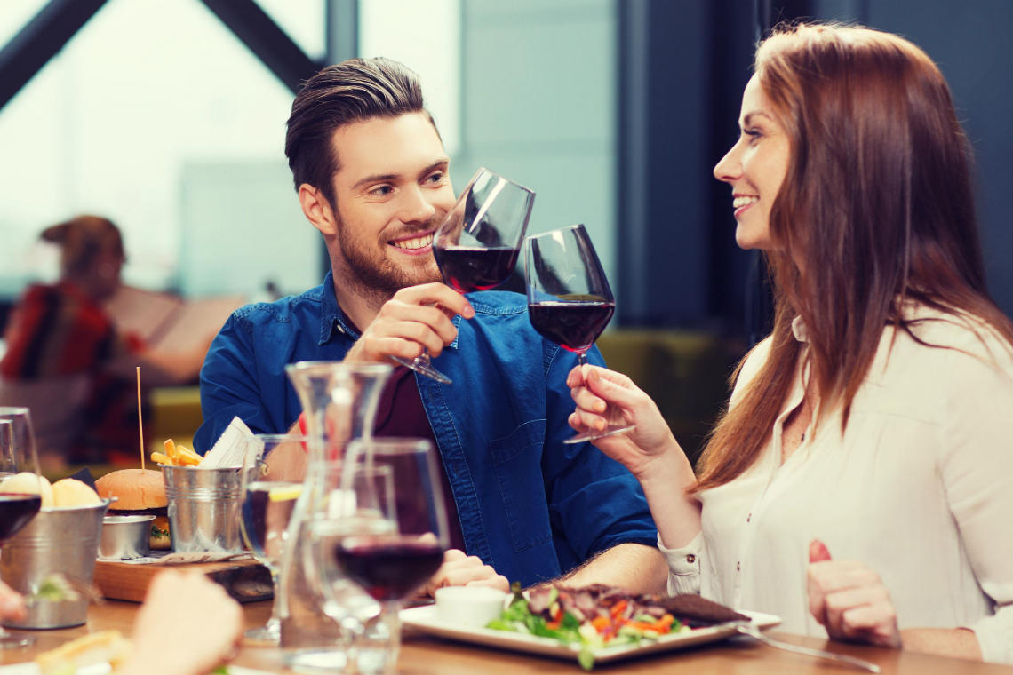 Couple out to dinner and toasting with red wine